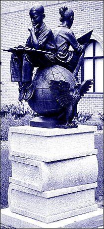 Statue of two students reading, sitting on a globe with outstretched wings facing out between the two children on one side.